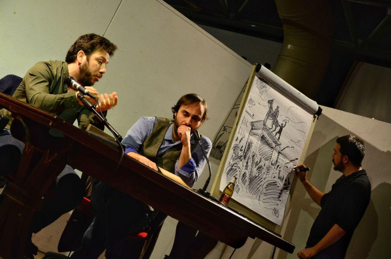 """Io e Alberto parliamo mentre Alessandro finisce di disegnare la """"Festa di liberazione"""" di Ernesto."""
